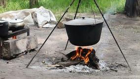 Werferlager, kochend auf einem Feuer stock footage