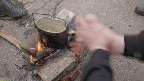 Werferlager, kochend auf einem Feuer, Mann, der seine Hände über einem Feuer wärmt stock video footage