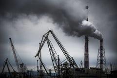 Werft am bewölkten Tag mit dem Rauche, der vom Kraftwerk pumpt Lizenzfreie Stockbilder