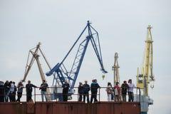 Werftarbeitskräfte auf dem Kai auf einem Hintergrund von Kränen Lizenzfreies Stockfoto