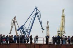 Werftarbeitskräfte auf dem Kai auf einem Hintergrund von Kränen Stockbilder