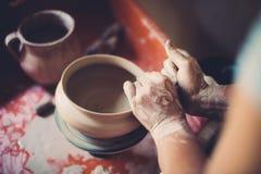 Werk in een aardewerkworkshop, de handen die van de vrouw tot keramiek het leiden stock foto's