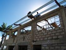 Werk in uitvoering die dak op een concreet gebouw construeren Stock Afbeelding
