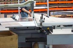 Werk in uitvoering die hout zagen close-up die van blad is ontsproten Een machine die hout, spaanplaat en houtvezelplaat zaagt royalty-vrije stock afbeelding