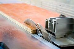 Werk in uitvoering die hout zagen close-up die van blad is ontsproten Een machine die hout, spaanplaat en houtvezelplaat zaagt stock afbeeldingen