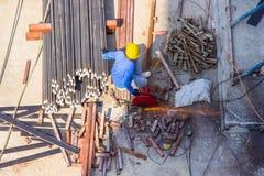 Werk van de het staalsnijmachine van het arbeidersgebruik het elektrische industriële in de bouw van de gebiedsbouw royalty-vrije stock afbeelding