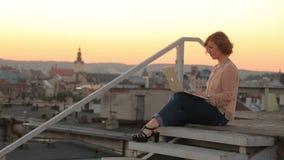 Werken van de manier overbruggen de jonge vrouw met laptop op de oude stad op zonsondergang Stedelijke cityscape op achtergrond stock video