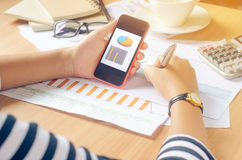 Werkend aan een bureau numeriek bij de mobiele analyse, financiële boekhouding Het grafisch voorstellen van Internet, stock foto's