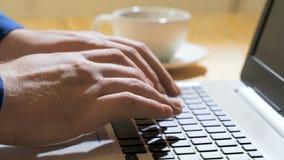 Werkend aan laptop computer, die op toetsenbord, moderne bureauzaken typen De mensen dient een beige sweaterdruk op in stock video