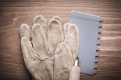 Werkend handschoen en stopverfmes op houten raad Stock Fotografie