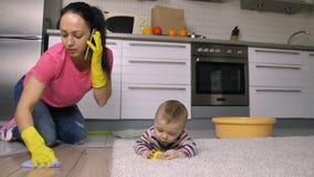 Werkend mamma die huishoudelijk werk doen terwijl gevende baby stock video