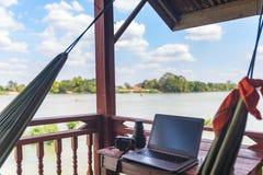 Werkend met laptop aan houten balkon in toeristentoevlucht met het hangen van hangmat op de Mekong Rivier, Laos Concept millenial stock foto's