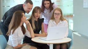 Werkend team van vijf mensen, bekijk laptop en bespreek het bedrijfsidee stock videobeelden