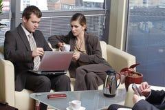 Werkende Bedrijfsmensen die in het bureau en het spreken zitten royalty-vrije stock afbeelding
