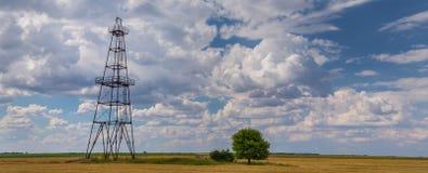 Werkende die olie en gasput op bewolkte hemel wordt geprofileerd Stock Afbeeldingen