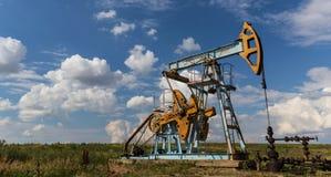 Werkende die olie en gasput op bewolkte hemel wordt geprofileerd royalty-vrije stock foto's