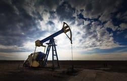 Werkende die oliebron op dramatische bewolkte hemel wordt geprofileerd Stock Foto's