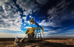 Werkende die oliebron op dramatische bewolkte hemel wordt geprofileerd royalty-vrije stock foto