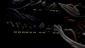 Werkende Ethernet-schakelaar in een donkere ruimte van het gegevenscentrum Vele opvlammende groene lampen stock video