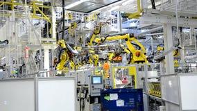 Werkende gele robotachtige wapens in de fabriek stock footage
