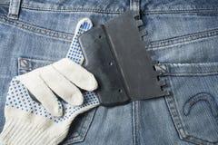 Werkende handschoen met het pleisteren van hulpmiddel op de achtergrond van jeans Hoogste mening Royalty-vrije Stock Foto's