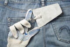 Werkende handschoen met het pleisteren van hulpmiddel op de achtergrond van jeans Hoogste mening Stock Afbeeldingen