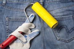 Werkende handschoen met het pleisteren van hulpmiddel op de achtergrond van jeans Hoogste mening Stock Foto