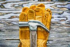 Werkende handschoenenklauwhamer op houten raad Stock Fotografie