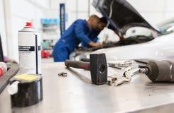 Werkende hulpmiddelen en mensen die auto herstellen op workshop Royalty-vrije Stock Foto's