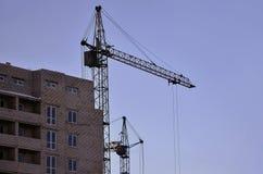 Werkende lange kranen binnen plaats voor met lange gebouwen in aanbouw tegen een duidelijke blauwe hemel Kraan en de bouw het wer Royalty-vrije Stock Foto