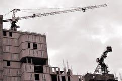 Werkende lange kranen binnen plaats voor met lange gebouwen in aanbouw tegen een duidelijke blauwe hemel Kraan en de bouw het wer Royalty-vrije Stock Foto's