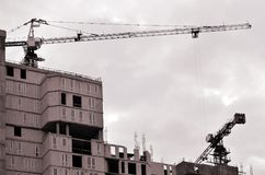 Werkende lange kranen binnen plaats voor met lange gebouwen in aanbouw tegen een duidelijke blauwe hemel Kraan en de bouw het wer Stock Afbeelding