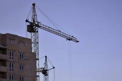 Werkende lange kranen binnen plaats voor met lange gebouwen in aanbouw tegen een duidelijke blauwe hemel Kraan en de bouw het wer Stock Foto