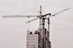 Werkende lange kranen binnen plaats voor met lange gebouwen in aanbouw tegen een duidelijke blauwe hemel Kraan en de bouw het wer Royalty-vrije Stock Afbeelding
