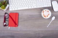 Werkende lijst met toetsenbord, nota's, pen, glazen en roomijs i stock fotografie