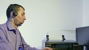 Werkende mens in call centresteun voor computer met hoofdtelefoons en microfoon stock videobeelden
