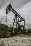 Werkende oliepomp met bewolkte achtergrond Royalty-vrije Stock Foto's