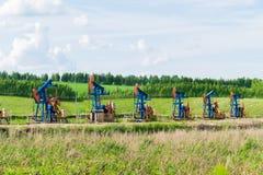 Werkende oliepompen ter plaatse onder de groene gebieden stock afbeelding