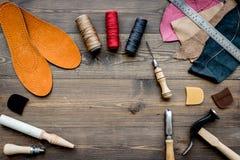 Werkende plaats van schoenmaker Huid en hulpmiddelen op bruine houten bureau hoogste mening als achtergrond copypace stock foto
