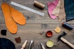 Werkende plaats van schoenmaker Huid en hulpmiddelen op bruine houten bureau hoogste mening als achtergrond copypace royalty-vrije stock foto