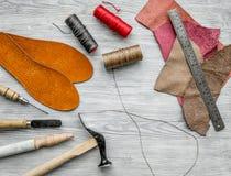 Werkende plaats van schoenmaker Huid en hulpmiddelen op grijze houten bureau hoogste mening als achtergrond stock fotografie