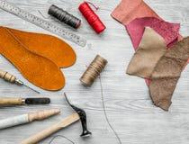 Werkende plaats van schoenmaker Huid en hulpmiddelen op grijze houten bureau hoogste mening als achtergrond stock afbeeldingen