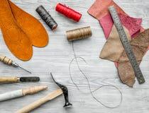 Werkende plaats van schoenmaker Huid en hulpmiddelen op grijze houten bureau hoogste mening als achtergrond royalty-vrije stock foto's