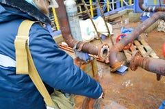 Werkende reparaties roestige pijpen en flenzen bij petrochemische pla stock afbeeldingen