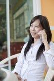 Werkende vrouw die mobiele telefoon spreken royalty-vrije stock afbeelding