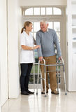Werker uit de hulpverlening die de Bejaarde Hogere Mens helpt Stock Foto