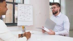 Werkgever die gesprek met werknemer hebben op kantoor stock video