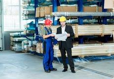 Werkgever en arbeider met plan in gesprek Stock Afbeelding