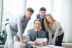 Werkgever met digitale tablet en zijn commercieel team Stock Fotografie
