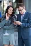 Werkgever met mobiele telefoon en zijn secretaresse. Zijn teleurgesteld. Stock Foto